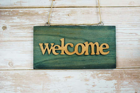 Welcome sign hanging on wooden background
