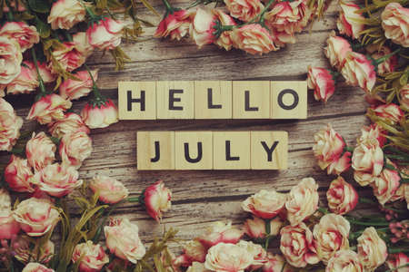 Hello July alphabet letters with flower decoration on wooden background Фото со стока