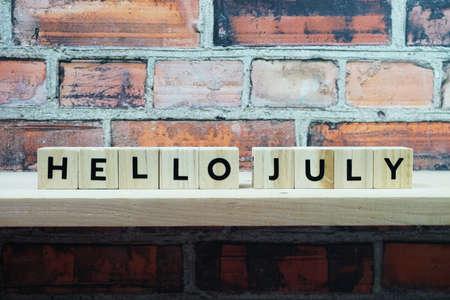 Hello July alphabet letter on shelves wooden background
