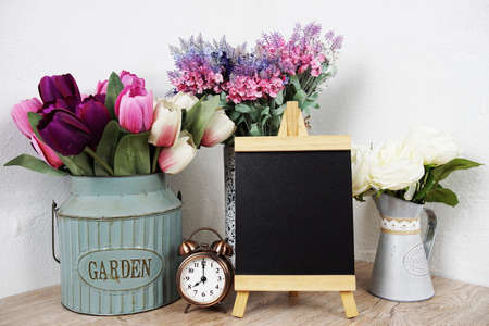 Empty easel chalkboard sign mockup with alarm clock and flower decoration