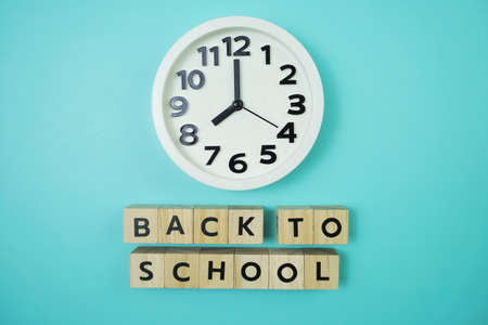 Back to School with clock on blue background Фото со стока