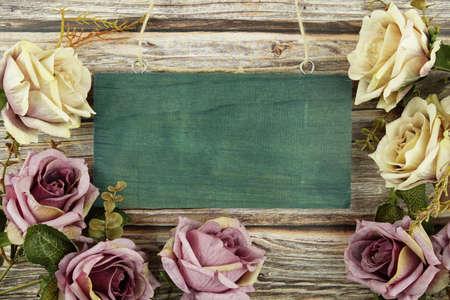 Pink roses flowers border frame on wooden background