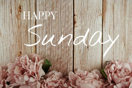 Happy Sunday typography text with pink flowers bouquet on wooden background