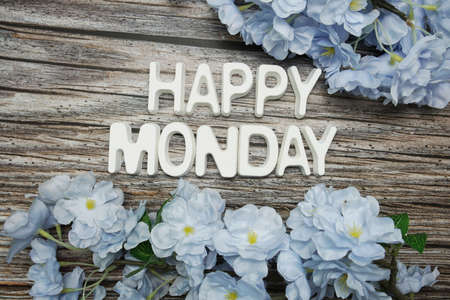 Happy Monday alphabet letter with flower decoration on wooden background