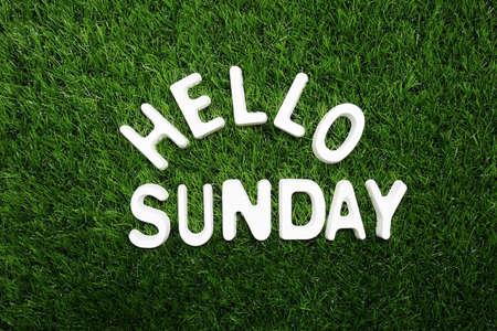 Hello Sunday alphabet letter on green grass background