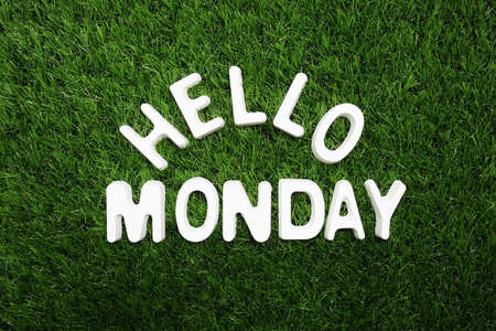 Hello Monday alphabet letter on green grass background
