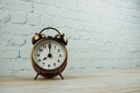 Vintage alarm clock with space copy on wooden background