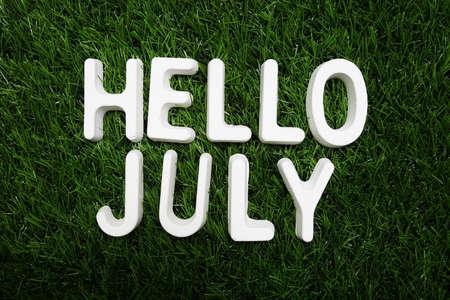 Hello July alphabet letter on green grass background