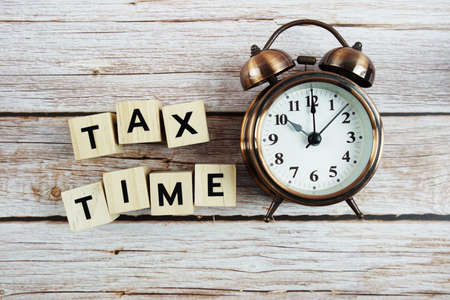 Tax Time with alarm clock with space copy on wooden background