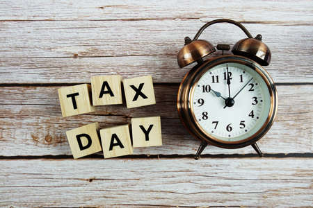 Tax Day Word alphabet letter And Alarm Clock on wooden background Фото со стока