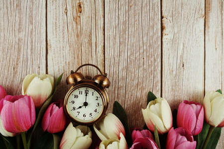 Vintage alarm clock with pink tulip flower bouquet on wooden background