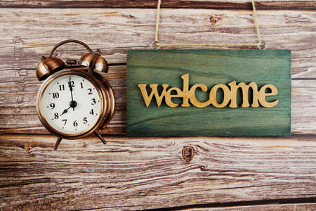 Welcome Sign and alarm clock on wooden background Фото со стока