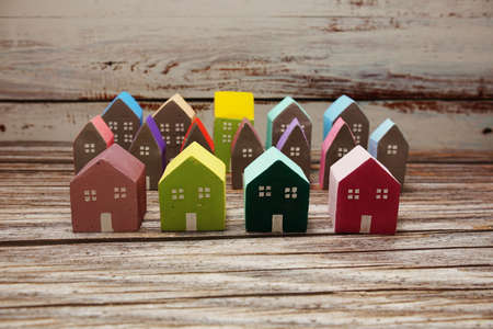 Colorful miniature house arranged on wooden background Фото со стока