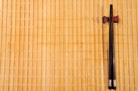 Two chopsticks on sushi mat