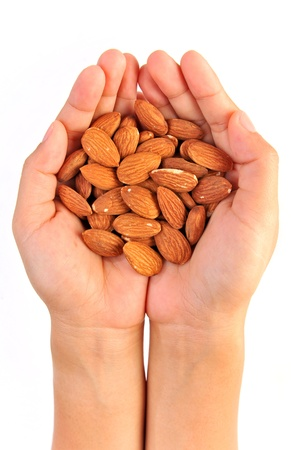Almonds in hand isolated on white photo