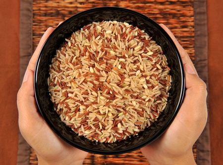 Brown Rice in womans hands photo