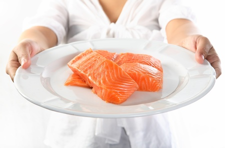 fresh salmon fillet on black plate, isolated on white