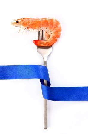 Shrimp on fork and ribbon, photo on the white background photo