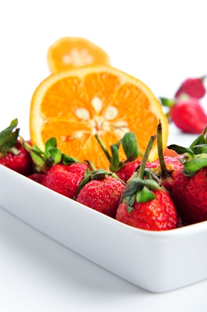pile of oranges with strawberries on white background Stock Photo