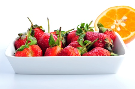 a pile of oranges with strawberries on white background photo