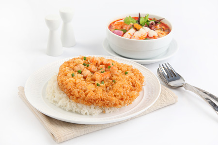 fried omelet topped on rice and seafood Tom Yum soup photo