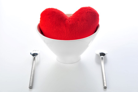Red heart in plate with fork and spoon photo