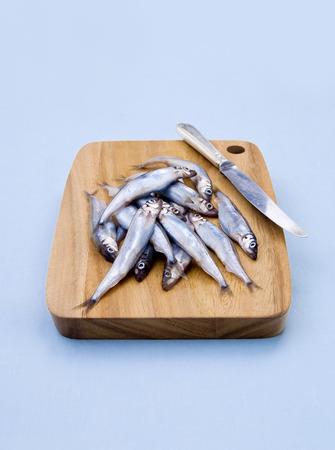 cichlidae: Fresh fishes on wooden cutting board