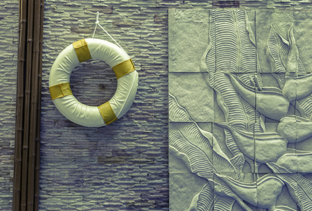 Life buoy hanging on  wall - vintage filter Stock Photo