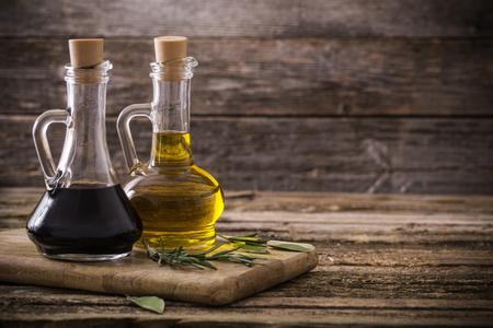 オリーブ オイルとバルサミコ酢の木製の背景 写真素材