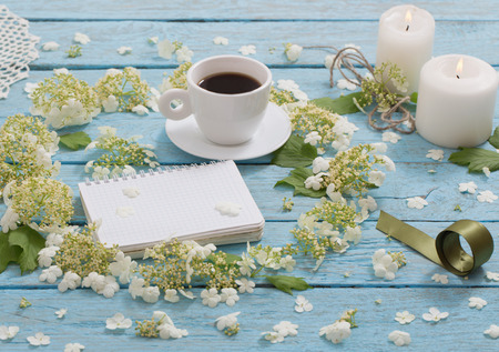 beautiful composition with a cup of coffee and white flowers on a blue wooden background
