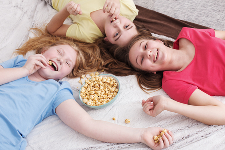 cartoons television: happy little girls  eating popcorn at home