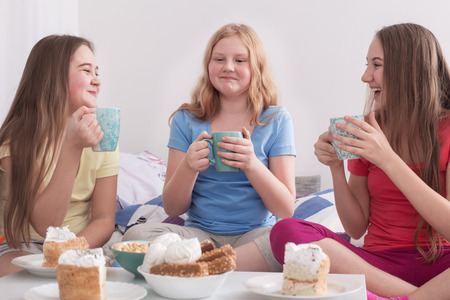 teenage girls drinking tea and eating sweets at home
