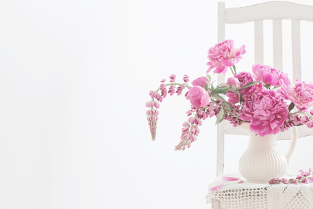 Peony flowers in a vase on vintage chair Stock Photo