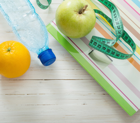 fruits in water: Scales, fruits, water on the white wooden background