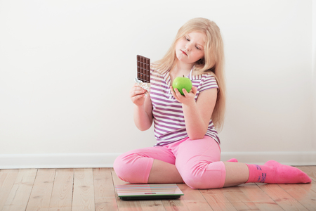 happy girl  with scales, fruits and chocolate Standard-Bild