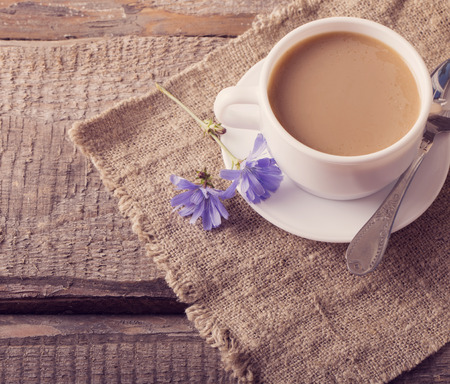chicory coffee: Cup of tea with chicory on wooden background