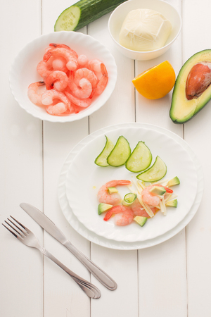 Cooked shrimps with avocado and mozzarella on white wooden table