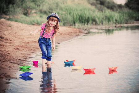smile child playing with paper boats in a river Reklamní fotografie