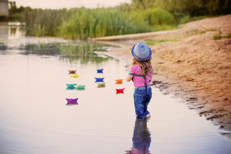 child playing with paper boats in a river