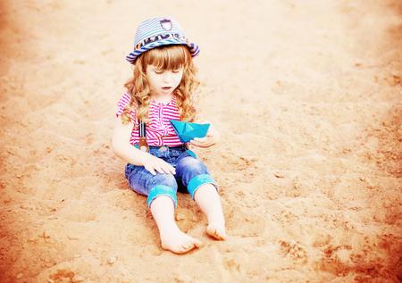 child playing with paper boats on sand Reklamní fotografie