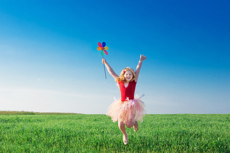 educacion ambiental: Niña saltando y sosteniendo una flor de juguete