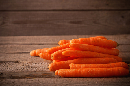 Organic Carrots on wooden background Stock Photo