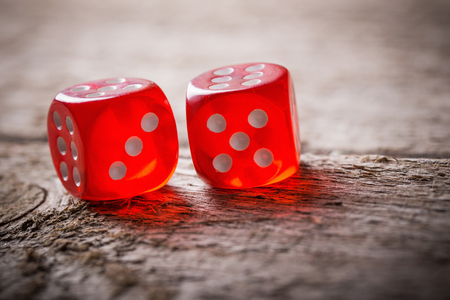 Pair of thrown red dices on old wooden table Stock Photo