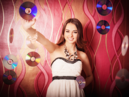 portrait of beautiful brunette girl with multiple shiny cds Stock Photo