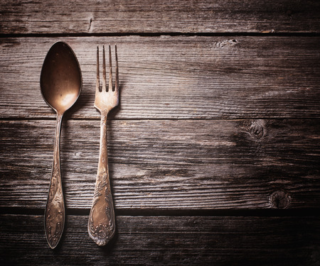 Old fork and spoon on wooden background Stock Photo