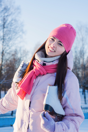 beautiful brunette girl with ice skate outdoor Stock Photo