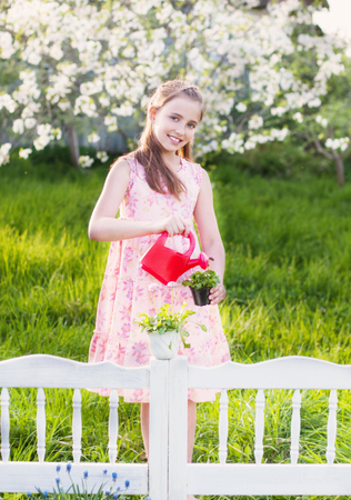 Beautiful girl watering spring flowers Stock Photo
