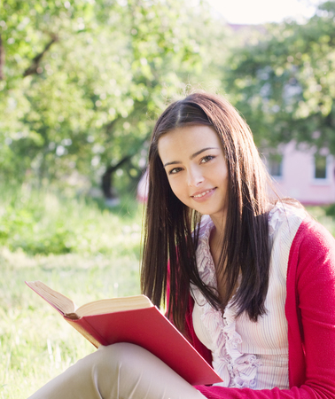 sprightly: beautiful girl reads book in a park Stock Photo