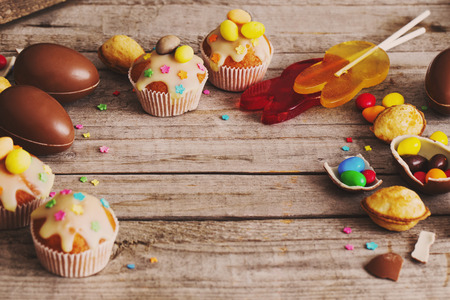 Chocolate Easter Eggs and Cake Over Wooden Background