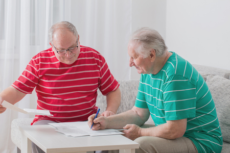 couple on couch: Two elderly men with documents